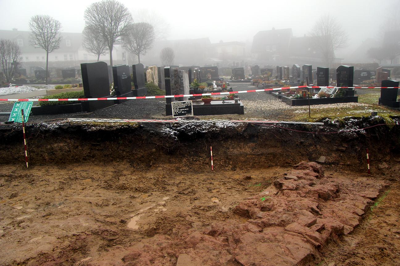 Ausgrabungsfläche an der Pfarrkirche Mariä Himmelfahrt in Teuschnitz mit Resten der ehemaligen Friedhofsmauer